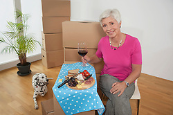 Senior woman moving into new home celebrating with wine, Bavaria, Germany