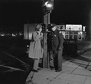 Y-501129-01. Police Rookie story.  Officers Gross & Benson. November 29, 1950. First prize AP feature. Police call box at the corner of NE Grand & Glisan. (due to construction, this location is approximately at Grand and Lloyd Way NE now)