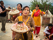 31 JULY 2015 - KATHMANDU, NEPAL:  Nepalese Hindus make an offering at Swayambhunath Stupa, a large Buddhist stupa in Kathmandu. Parts of the stupa were badly damaged in the Nepal earthquake of 2015 but it is still open for religious devotees and tourists. Construction of the stupa started in the 1600s. Even though it is a Buddhist stupa, there are several Hindu shrines in the complex and Hindus come to the stupa to worship every day.  PHOTO BY JACK KURTZ