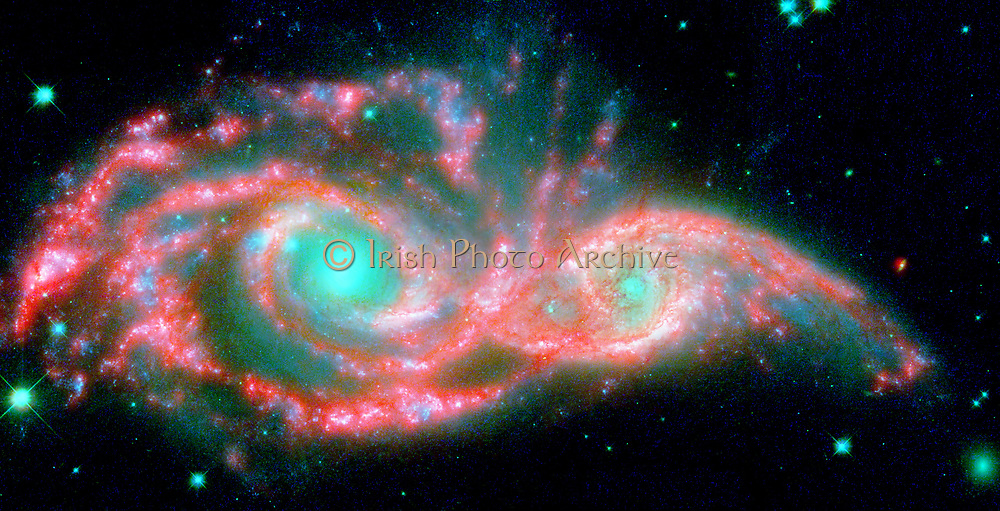 These shape-shifting galaxies have taken on the form of a giant mask. The icy blue eyes are actually the cores of two merging galaxies, called NGC 2207 and IC 2163, and the mask is their spiral arms. The false-collared image consists of infrared data from NASA's Spitzer Space Telescope (red) and visible data from NASA's Hubble Space Telescope (blue/green). NGC 2207 and IC 2163 met about 40 million years ago. The two galaxies are tugging at each other, stimulating new stars to form. Eventually, this cosmic ball will come to an end, when the galaxies meld into one. The dancing duo is located 140 million light-years away in the Canis Major constellation.
