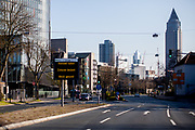 """Empty streets during a Saturday afternoon in Frankfurt am Main. A public information board announces: """"Keep distance, stay at home, stay healthy""""."""