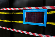 A detail of hazard tape marks the dangerous presence of Asbestos at a business at Spitalfields, on 26th June, in London, England.