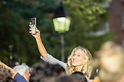New York, NY – 16 September 2019. Massachusetts Senator and Democratic Presidential candidate Elizabeth Warren drew a large and enthusiastic crowd at a speech for her increasingly popular 2020 presidential campaign in New York's Washington Square. Warren got the support of the Working Families Party earlier in the day. A woman takes a selfie with the Washington Square Arch in the background.