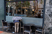 In front of a cafe whose slogan is Heres to a Long Cold Summer, an anonymous person bends over while holding an umbrella during Spring rainfall in Holborn, on 24th May 2021, in London, England.