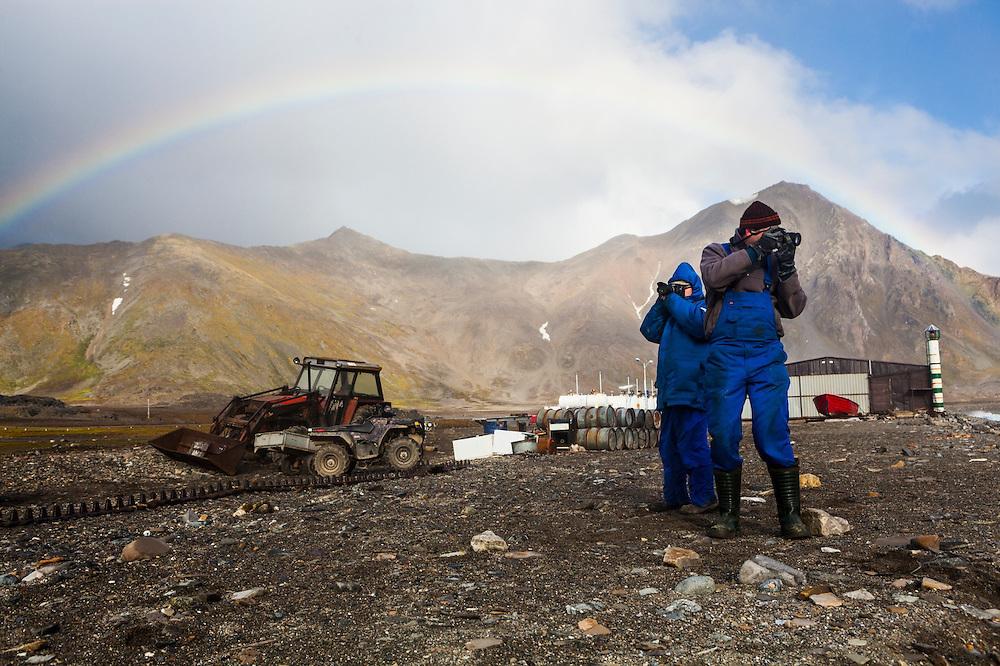 Adam Nawrot (right) and Franciszek Krzeminski take pictures during a scenic storm break at the Polish Polar Station in Hornsund, Svalbard.