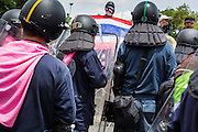 07 AUGUST 2013 - BANGKOK, THAILAND: A Thai anti-government protester with a Thai flag confronts riot police at a checkpoint near the parliament building. About 2,500 protestors opposed to an amnesty bill proposed by Thailand's ruling party marched towards the Thai parliament in the morning. The amnesty could allow exiled fugitive former Prime Minister Thaksin Shinawatra to return to Thailand. Thaksin's supporters are in favor of the bill but Thai Yellow Shirts and government opponents are against the bill. Thai police deployed about more than 10,000 riot police and closed roads around the parliament. Although protest leaders called off the protest rather than confront police, a few people were arrested for assaulting police when they tried to break through police lines. Several police officers left the scene under medical care after they collapsed in the heat.     PHOTO BY JACK KURTZ