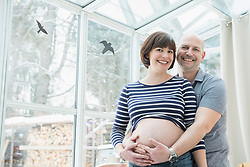 Portrait of man holding belly of pregnant wife