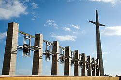 """È stata inaugurata il 1° luglio 2004, la nuova Chiesa di San Pio da Pietrelcina progettata dall'architetto Renzo Piano. Esattamente 45 anni prima, nel 1959,  veniva inaugurata la chiesa """"grande"""" di Santa Maria delle Grazie. .Sorta a fianco del santuario e convento in cui visse il frate, ha la forma di una conchiglia e la sua pianta ricorda quella della spriale archimedea. Enormi archi parto dal perimetro esterno e terminano nel fulcro della """"conchiglia"""" dove è posto l'altare. Possenti staffe d'acciaio, ancorate agli archi, sorreggono la volta che ricoperta di rame preossidato espone alla vista un intenso un colore verde-rame.   .Con i suoi 6000 mq, è la seconda chiesa più grande in Italia per dimensioni, dopo il Duomo di Milano. Può ospitare oltre 7000 persone e per la sua realizzazione sono state impiegati 30.000 metri cubi di calcestruzzo, 1.320 blocchi in pietra di Apricena, 70.000 metri cubi di scavo in roccia, 60.000 chili di acciaio, 500 mq di vetro, 19.500 mq di rame preossidato. Ogni anno è meta di oltre sei milioni di pellegrini..Nella foto la struttura che fiancheggia la chiesa composta da un'alta croce e una serie di otto campanili stilizzati con altrettante campane."""