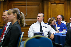© Licensed to London News Pictures. 23/10/2014. London, UK. A police commander listening Home Secretary Theresa May delivering a keynote speech during Policing and Mental Health National Summit at Central Hall Westminster in London on Thursday, 23 October 2014. In her speech, Home Secretary revealed new measures to change the way police forces deal with mental health patients. Photo credit : Tolga Akmen/LNP