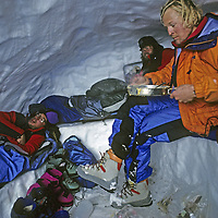 CORDILLERA SARMIENTO, Patagonia, Chile. Climbers eat last of their food in soggy snow cave during extended foul weather in this previously unexplored range. LtoR: Tyler Van Arsdell, Pete Garber, Philip Lloyd (MR).