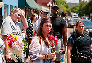 08072019 - Dayton, Ohio, USA: A group watches as Trump supporter drive a bus with flags supporting Trump down 5th Street at the site of Sunday morning's mass shooting that left 9 dead, and 2s7 wounded, Wednesday, August 7, 2019 in Dayton, Ohio. Trump visited a nearby hospital but did not visit the site of the shooting before flying to El Paso, Texas, which was also the site of a mass shooting.