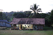 Surui modern village home at dusk with satellite dish and electricty<br /><br />An Amazonian tribal chief Almir Narayamogo, leader of 1350 Surui Indians in Rondônia, near Cacaol, Brazil, with a $100,000 bounty on his head, is fighting for the survival of his people and their forest, and using the world's modern hi-tech tools; computers, smartphones, Google Earth and digital forestry surveillance. So far their fight has been very effective, leading to a most promising and novel result. In 2013, Almir Narayamogo, led his people to be the first and unique indigenous tribe in the world to manage their own REDD+ carbon project and sell carbon credits to the industrial world. By marketing the CO2 capacity of 250 000 hectares of their virgin forest, the forty year old Surui, has ensured the preservation, as well as a future of his community. <br /><br />In 2009, the four clans and 25 Surui villages voted in favour of a total moratorium on logging and the carbon credits project. <br /><br />They still face deforestation problems, such as illegal logging, and gold mining which causes pollution of their river systems