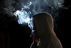 A silhouetted man smokes a cigarette. <br /><br />Picture posed by model - model release available.