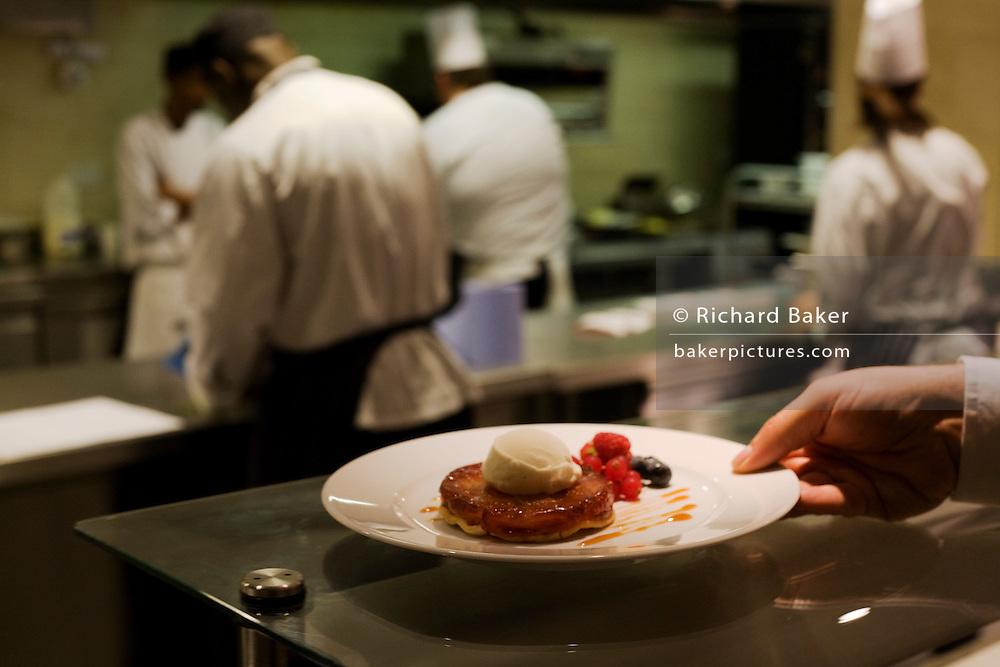 A waiter reaches for a finished tarte tatin desert dish at the Vivre restaurant in Sofitel.