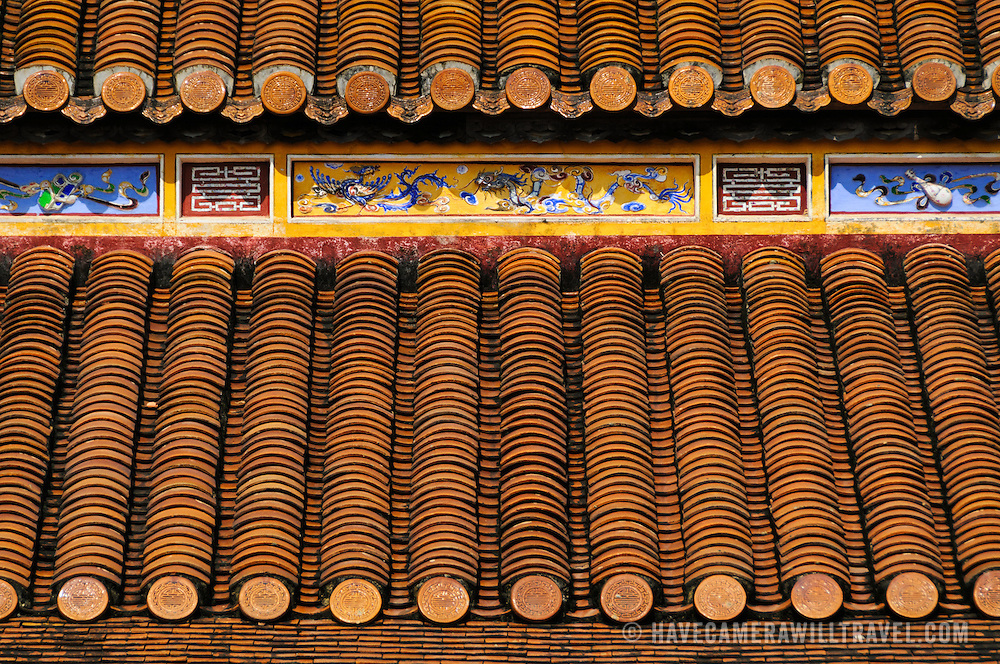 Carefully stacked roof tiles and ornate paintings on the roof of a restored building at the Imperial City in Hue, Vietnam. A self-enclosed and fortified palace, the complex includes the Purple Forbidden City, which was the inner sanctum of the imperial household, as well as temples, courtyards, gardens, and other buildings. Much of the Imperial City was damaged or destroyed during the Vietnam War. It is now designated as a UNESCO World Heritage site.