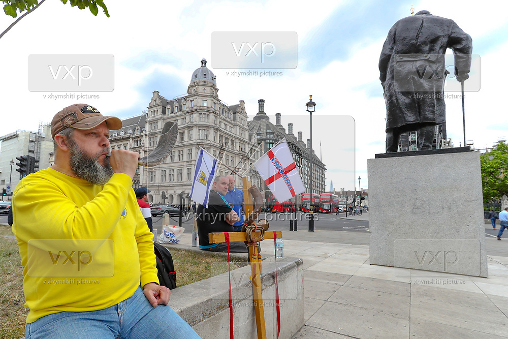 """A religiously motivated Christian man blows a horn in front of Winston Churchill statue beside a cross and English flag. """"I have the horn to warn my patriots to protect our heritage from anarchists,"""" he said, during a Black Lives Matter rally in Parliament Square in London, Tuesday, June 9, 2020. Anger against systemic levels of institutional racism has raged through the city, and worldwide; sparked by the death of George Floyd, who was killed in Minneapolis, US, by a policeman who restrained him with force on 25 May 2020. (Photo/ Vudi Xhymshiti)"""
