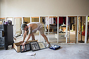 Erik Garza empties sets out photos to dry in his parents' flood damaged bedroom in Dickinson, Texas after Hurricane Harvey ravaged the area.