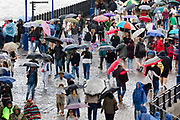 Crowds of tourists with umbrellas walking near the Tower of London during rain and wet weather in London, England on August 10, 2018