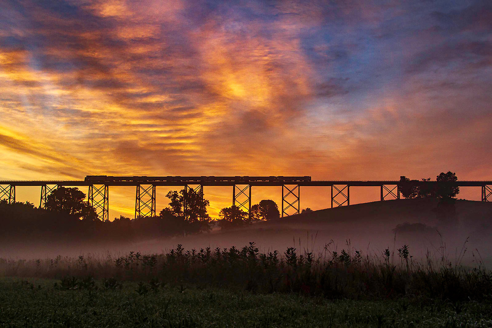 With a sunrise that should awaken some sleepy eyes on the early morning commute to Hoboken, Metro North train #46 crosses the valley over the Moodna Viaduct as fog starts to form below. <br /> <br /> While I had to get up plenty early to catch the summer sunrise, this train left Port Jervis at 5:05 and arrives in Hoboken at 7:14 which is an over 2 hour commute.