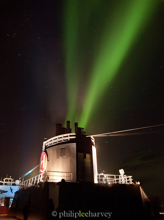 Aurora Borealis, the Northern Lights, over the chimney of a passenger cruise ship in the north of Norway