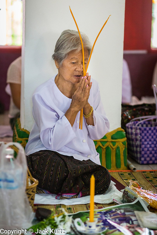 29 JUNE 2014 - DAN SAI, LOEI, THAILAND: A woman prays during a ceremony in Wat Ponchai on the last morning of the Ghost Festival. Phi Ta Khon (also spelled Pee Ta Khon) is the Ghost Festival. Over three days, the town's residents invite protection from Phra U-pakut, the spirit that lives in the Mun River, which runs through Dan Sai. People in the town and surrounding villages wear costumes made of patchwork and ornate masks and are thought be ghosts who were awoken from the dead when Vessantra Jataka (one of the Buddhas) came out of the forest. On the last day of the festival people participate in merit making ceremonies at the Wat Ponchai in Dan Sai and lead processions through town soliciting donations for the temple.    PHOTO BY JACK KURTZ