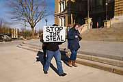 "26 DECEMBER 2020 - DES MOINES, IOWA: Four people marched around the Iowa State Capitol Saturday afternoon to protest the outcome of the November 3 general election in the United States. They are a part of the ""Stop the Steal"" movement which maintains that the election was stolen from Donald Trump by massive voter fraud. There is no evidence supporting their conspiracy theory. This is the 8th week Donald Trump supporters have marched around the Capitol. They've been there every week since the Nov. 3 election. More than 1,000 people showed up the first week, but the crowd has gotten smaller every week.     PHOTO BY JACK KURTZ"