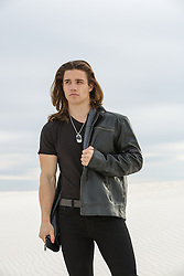 sexy man with long brown hair outdoors in a  leather jacket
