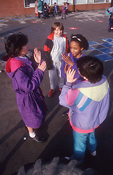 Junior school girls playing together in playground,
