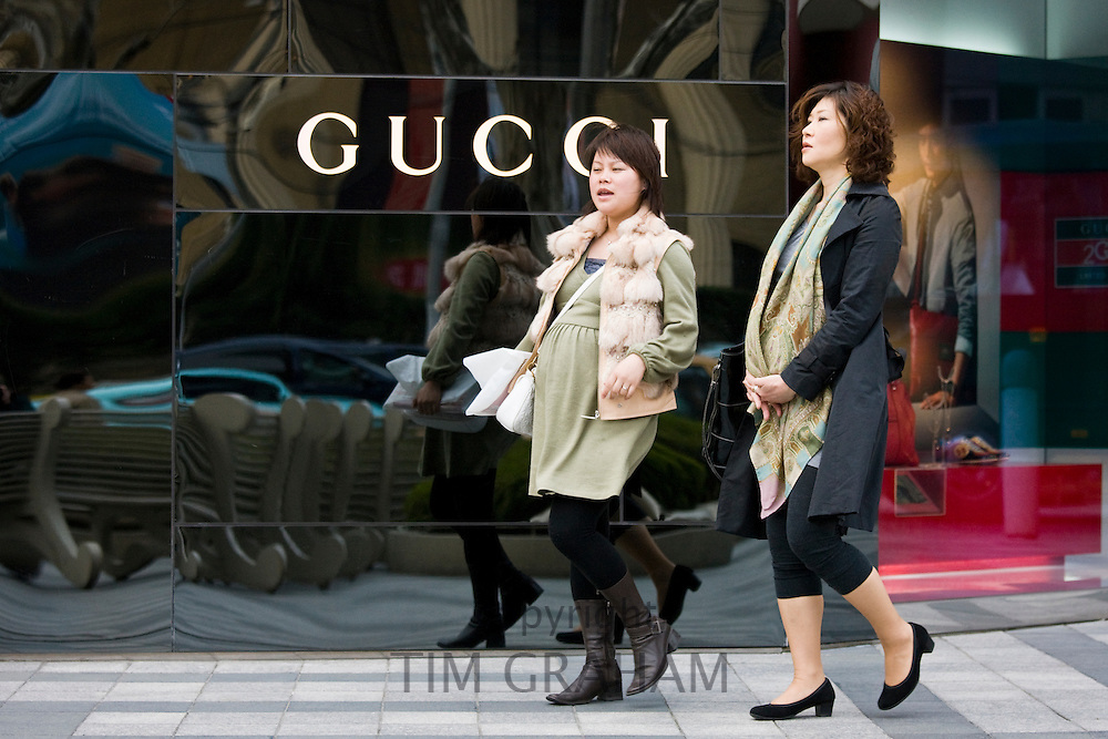 Pregnant women walk past Gucci deisgner clothes shop, on Nanjing Road, central Shanghai, China