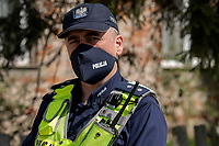 Policjant w maseczce ochronnej z napisem POLICJA podczas epidemii koronawirusa fot Michal Kosc / AGENCJA WSCHOD