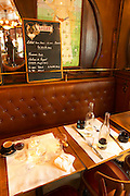 A lunch dining table after the meal is finished over. Empty glasses and carafes, paper table cloth emptied coffee cup napkin in the background: mirror and the menu with Lillet written on it The Bistrot du Peintre is an old fashioned Paris café cafe bar restaurant of art nouveau design with polished brass, mirrors and old signs