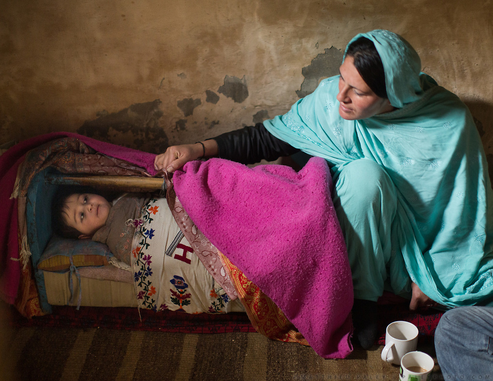 A woman watches over her newborn. In the old fortified village of Altit, over 1000 years old, Hunza region.