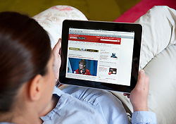 Woman using iPad tablet computer to read Der Spiegel German language magazine online