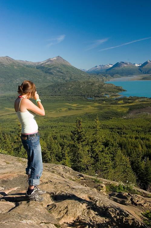 Alaska. Skilak Lake. A woman photographer takes in the stunning view over Skilak Lake.