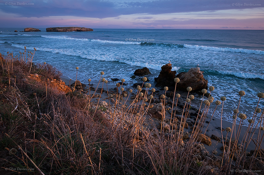 Waves and pebbly beach at dusk at Binigaus Beach and the tiny islands of Platja de Binicodrell, on the Mediterranean coast, South West Menorca.