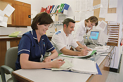Deputy Sister; staff nurse and dietician at workstation on spinal unit of hospital,