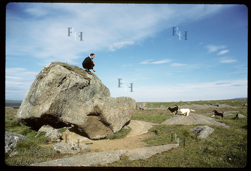 Farmer calls to his dogs as he kneels atop boulder that Grettir supposedly lifted in Saga; Bjarg Iceland
