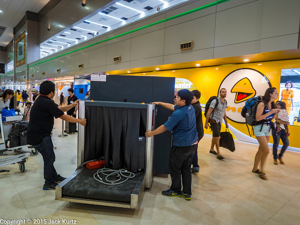 """24 DECEMBER 2015 - BANGKOK, THAILAND: Workers move a baggage x-ray machine through the new domestic terminal at Don Muang (also spelled Don Mueang) International Airport. The new terminal had its """"soft"""" opening Dec. 24. Don Muang is the airport used by low cost airlines serving Bangkok and is now the largest airport in the world for low cost carriers. In 2014, more than 21million passengers used Don Muang. Don Muang International Airport is the oldest airport in Asia and one of the oldest airports in the world. It started functioning as an airfield in 1914.     PHOTO BY JACK KURTZ"""