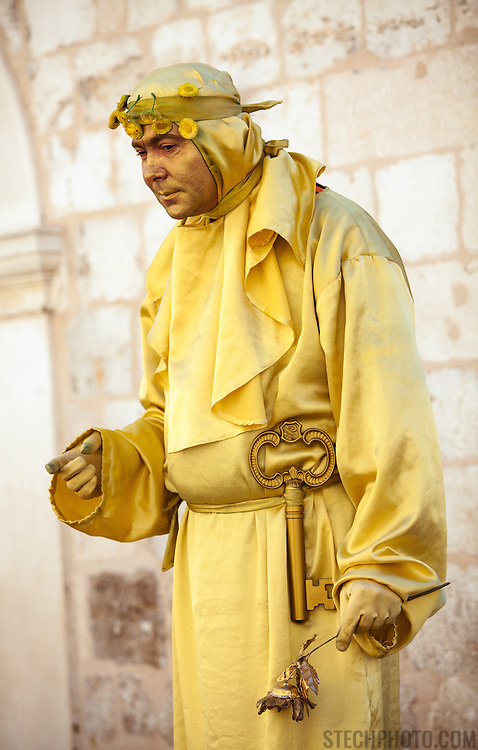 A living statue performer dressed in yellow on a street in the old city of Dubrovnik, Croatia.