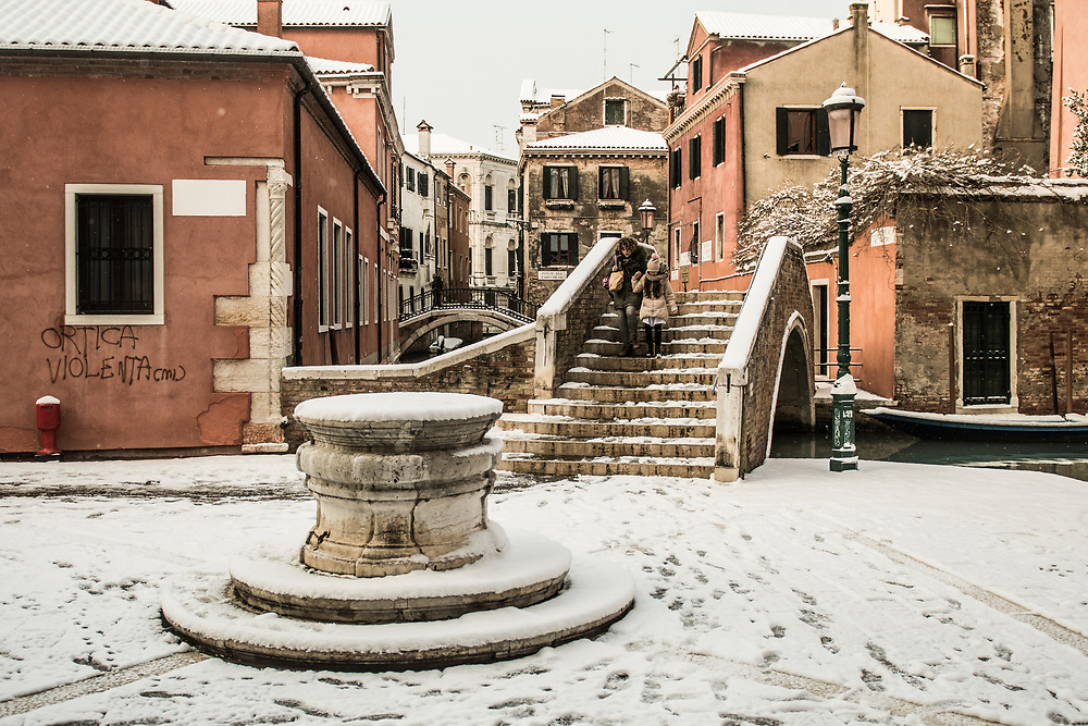 """VENICE, ITALY - 28th FEBRUARY/01st MARCH 2018<br /> A woman with her daughter walks cautiosly after a snowfall in Venice, Italy. A blast of freezing weather called the """"Beast from the East"""" has gripped most of Europe in the middle of winter of 2018, and in Venice A snowfall has covered the city with white, making it fascinating and poetic for citizen and tourists.   © Simone Padovani / Awakening"""