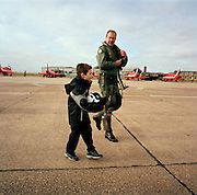 Young admirer carries helmet of pilot of the 'Red Arrows', Britain's Royal Air Force aerobatic team at RAF Scampton.