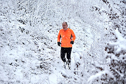 © Licensed to London News Pictures. 24/01/2021. Wendover, UK.  A man jogging near Coombe Hill as heavy snow falls in the Chilterns. The Met office has issued a yellow warning for snow covering most of the south of England until 23:59 tonight.   Photo credit: Cliff Hide/LNP