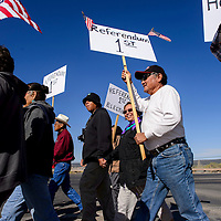042015       Cable Hoover<br /> <br /> Denny Tsosie, center, carries a sign calling for a referendum before the election during a protest in Window Rock Monday.