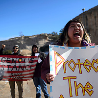 """Rebecca Jones leads a group of protesters in a chant of """"stand up, fight back"""" outside the Bureau of Land Management scoping meeting at the Navajo Nation Museum in Window Rock Friday."""