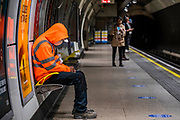 A worker in hi vis orange sits next to an advert for soldier of orange - behind him a womman removes her mask. Passenger numbers remain dramatically down on the tube, even during rush hour and even on teh first day of the easing of government guidance. Those who do travel attempt to obey the guidance on 2m social distancing and possibly around half wear masks -  despite isntructions from teh Mayor of London that he expects everyone to wear a mask on public transport. The 'lockdown' continues for the Coronavirus (Covid 19) outbreak in London.