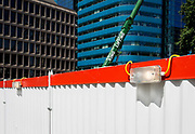 Construction hoarding, a crane and modern corporate architecture at Aldgate, on 17th Juy 2017, in the City of London, England.