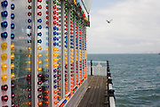 Brighton pier amusement arcade lights with the sea horizon beyond.
