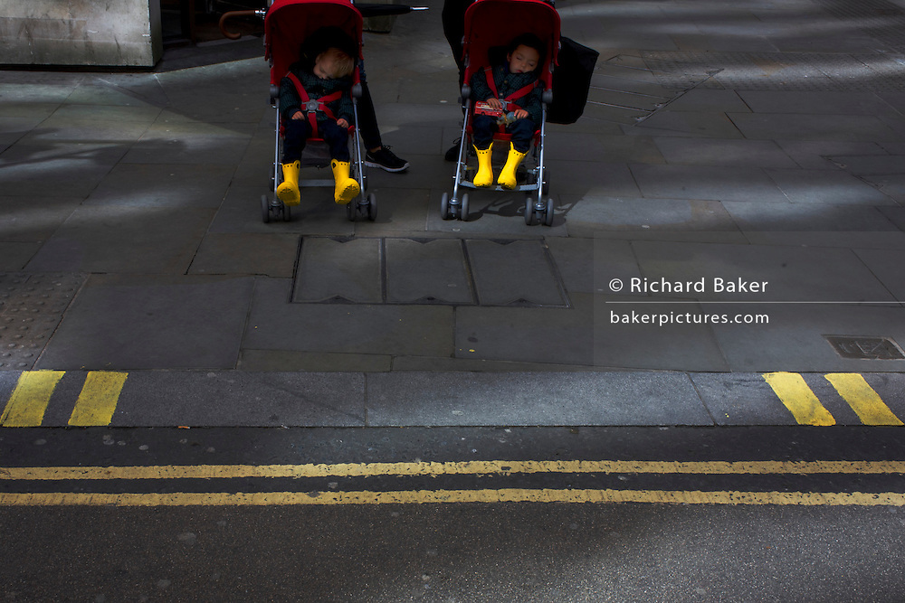 Two small children sleep in their respective buggies as unseen parents prepare to cross a street in the City of London.
