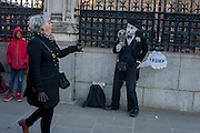Outside Britain's Palace of Westminster parliament, a young black boy looks a passing woman as a Charlie Chaplin character making a Donald trump joke, on the day of Trump's inauguration as the 45th US president, on 20th January, in Parliament Square, London borough of Westminster, England.