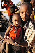 A child comforts his little brother, who is feverish with malaria in Kouakourou, Mali. The toddler wears charms and herbs to ward off illness.